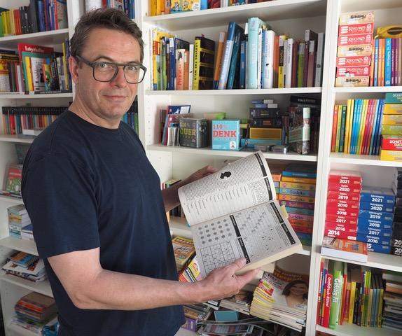 Rätsel-Erfinder Stefan Heine vor einem Regal voller Rätselbücher, -spiele & Co. Foto: Christoph Schumann, 2021