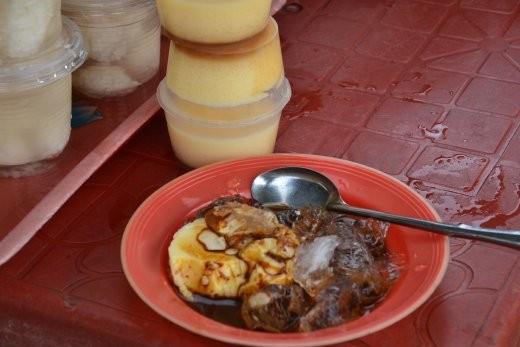 Vietnamesische Crème Caramel an einem kleinen Stand auf dem Markt. Mit Kaffeesirup und crushed ice drüber.
