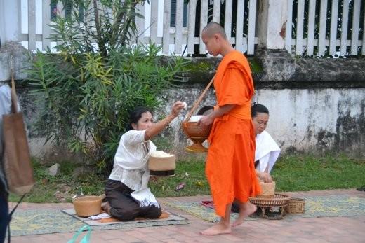Die Frauen sitzen alle nebeneinander am Boden und füllen die Bronzeschüsseln der Mönche.