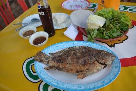 Grillfisch mit Zitronengras gefüllt. Wird mit Kräutern,m Salat, Sauce etc. in diesen dünnen Reismehlfrühlingsrollenteig gewickelt.