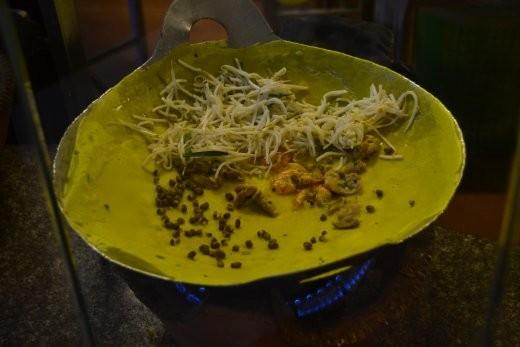 Banh Xeo. Ein dünner, knuspriger Crèpe mit Schweinefleisch, Shrimp, Sprossen und Bohnen.