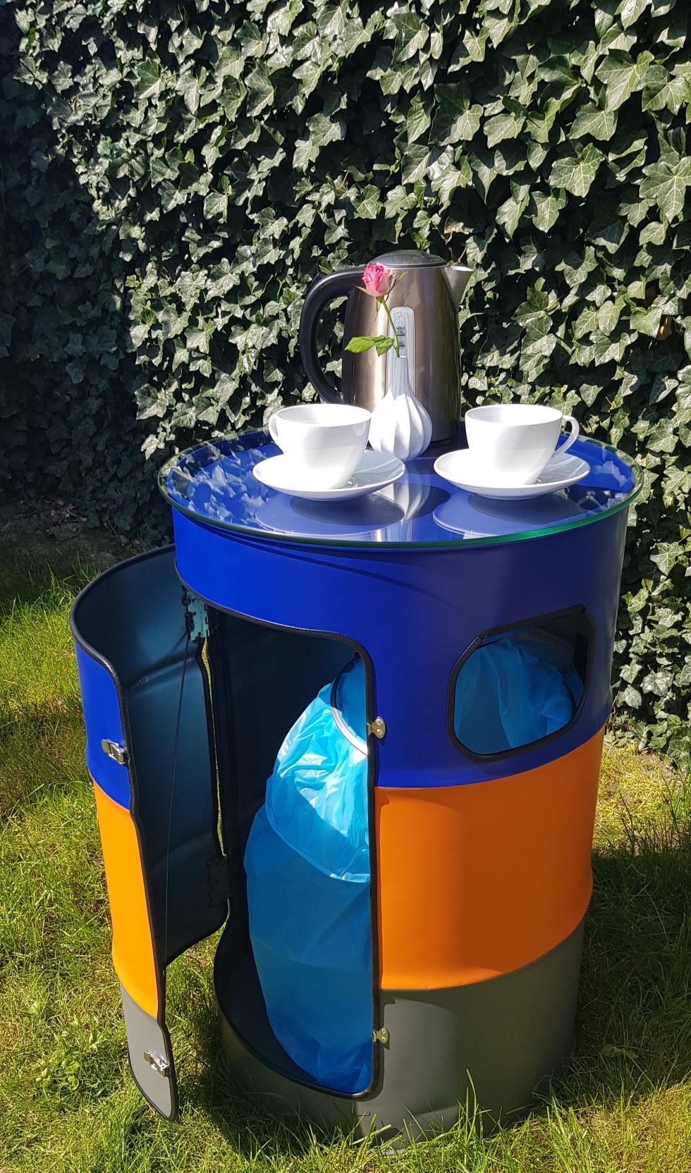 Kaffeetisch mit Mülleinwurf aus einem Ölfass recycelt. Der Müllsack wird durch eine integrierte Halterung ausgewechselt. Außen ist es ein schicker Kaffeetisch mit einer Glasplatte