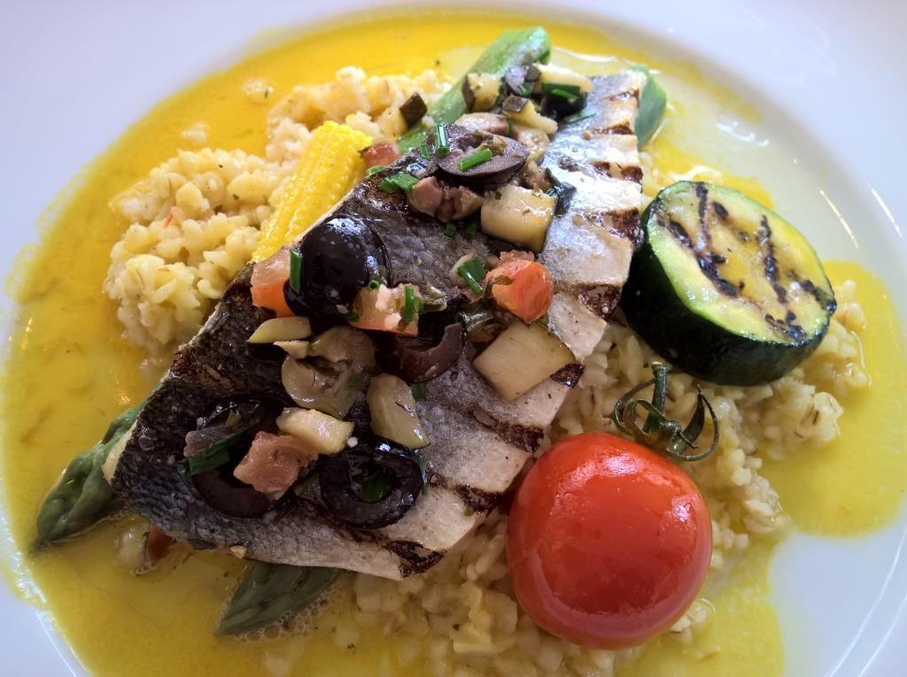 Gegrilltes Seebarschfilet, Gemüsewürfel und Bulgur mit Safran parfümiertem Olivenöl abgerundet