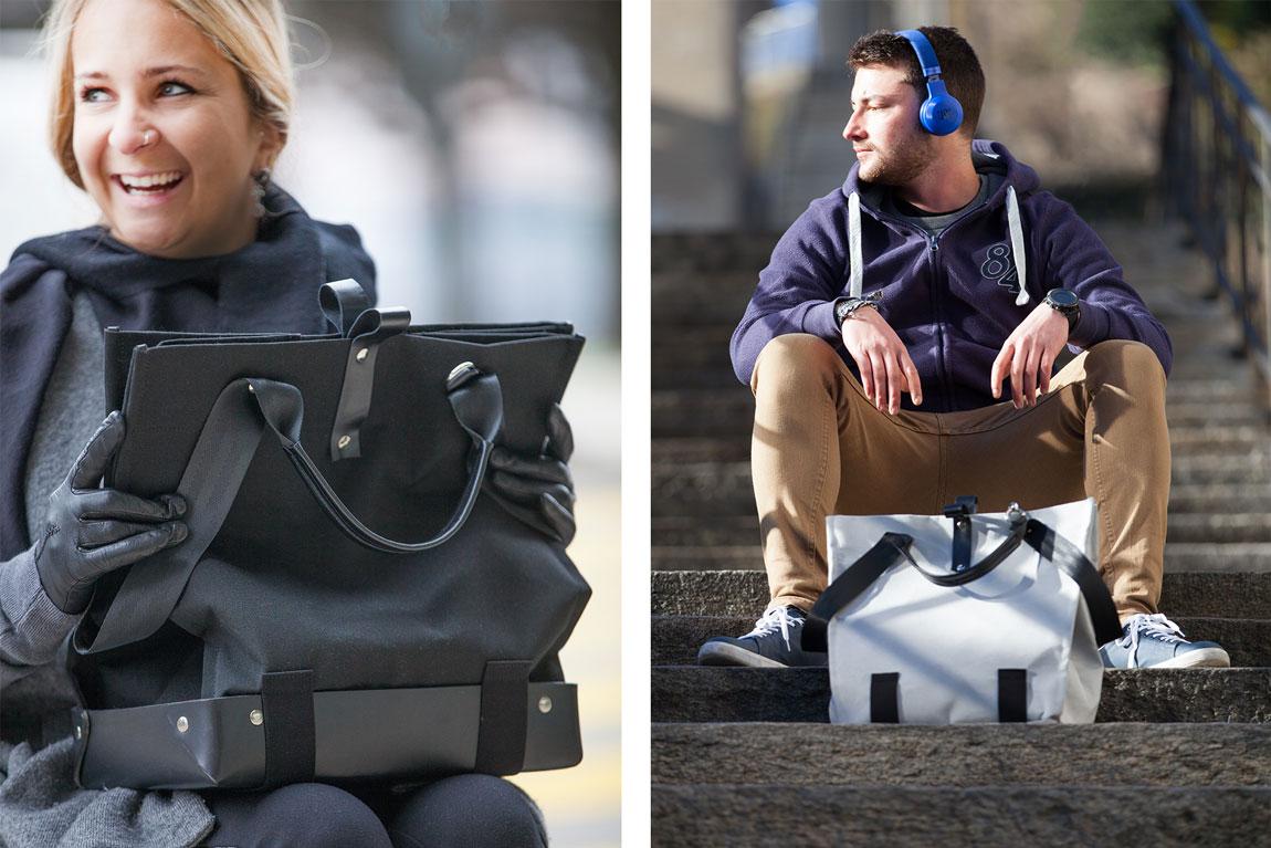 Eine elegante Frau im Rollstuhl hält die Trasporta-Tasche Jet Black. Ein Mann sitzt auf einer Treppe mit einer grauen Trasporta-Tasche zu seinen Füßen. Trasporta bag; Rollstuhltasche, Umhängetasche und Tragetasche in einem.