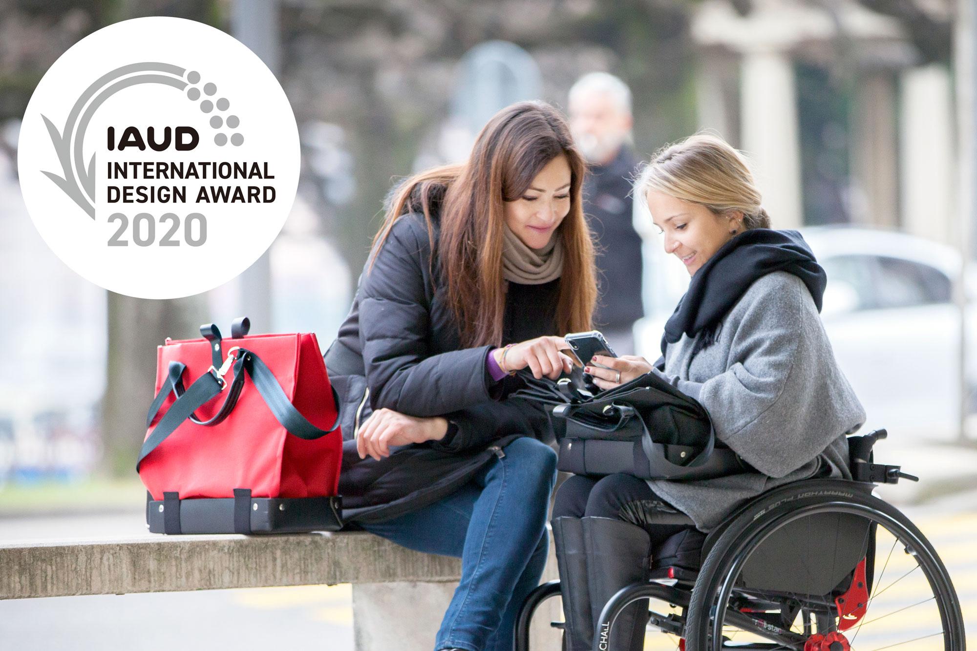 Donna elegante seduta su una sedia a rotelle con in braccio la borsa Trasporta bag colore Estate Blue. Borsa per sedia a rotelle, borsa a tracolla e borsa a mano tutto in uno.