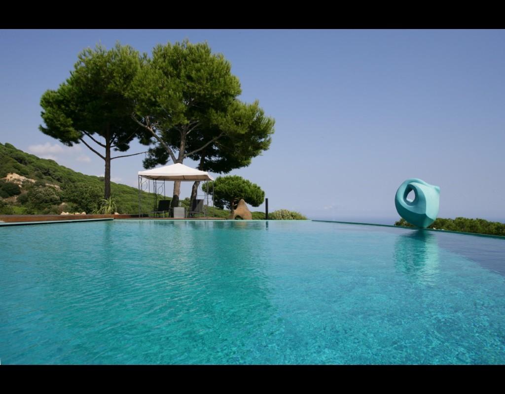 Vista piscina, escultura y pérgola norte
