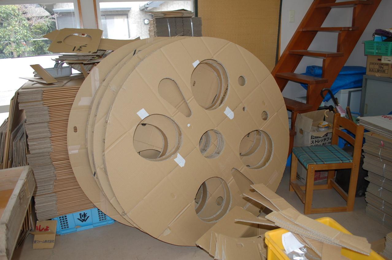 直径1.4mの動輪。ダンボール6枚重ねの外装用パネルに穴を開ける。