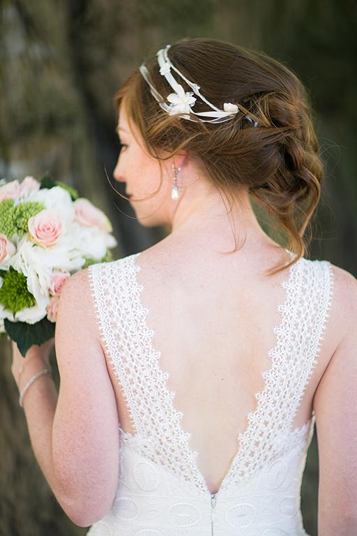 Braut im Brautkleid von hinten mit Brautstrauß in der Hand
