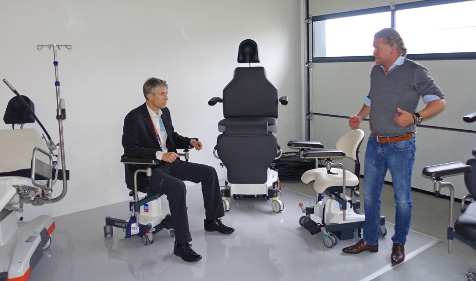 Werner sitzt in der Firma von Herrn Scherrieble (re. im Bild) zur Probe auf dem Operateurstuhl.