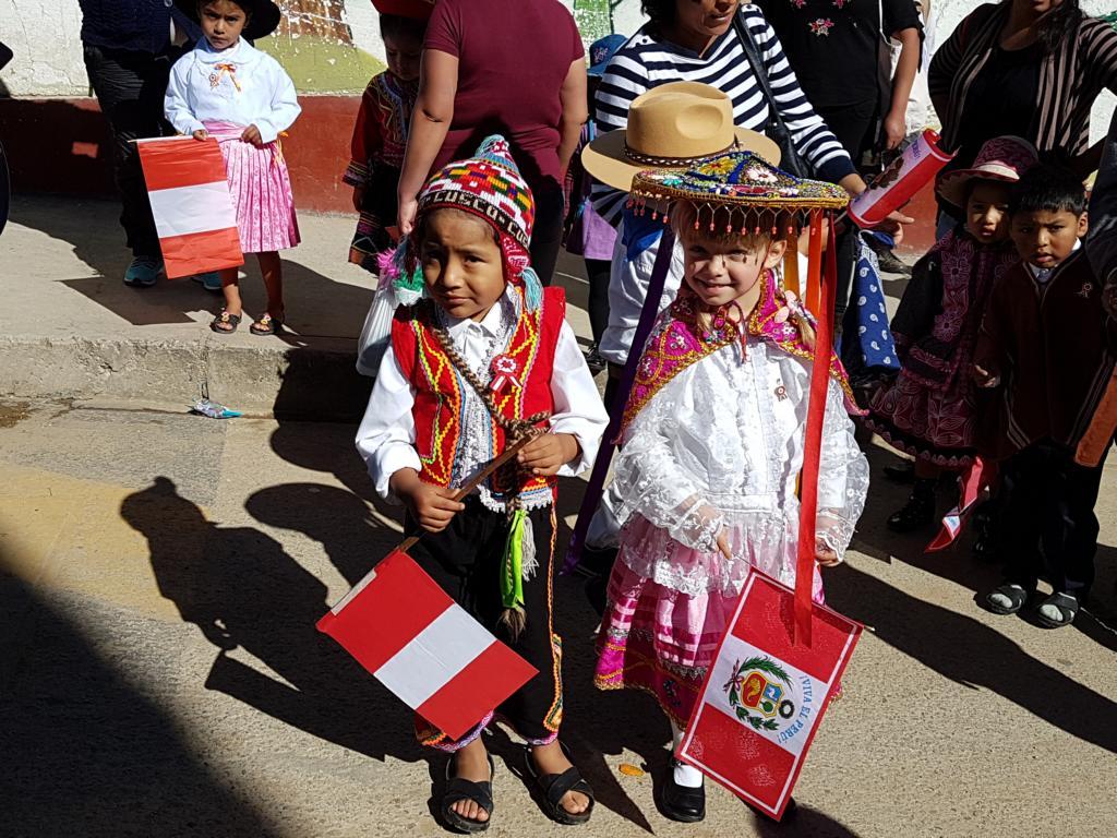 Sie zeigen typische Trachten aus verschiedenen Regionen Perus.