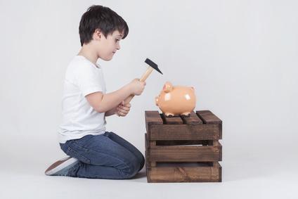 Kleiner Junge zerschlägt ein Sparschwein mit einem Hammer