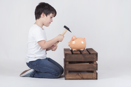 Boy Destroys a Piggy Bank with a Hammer