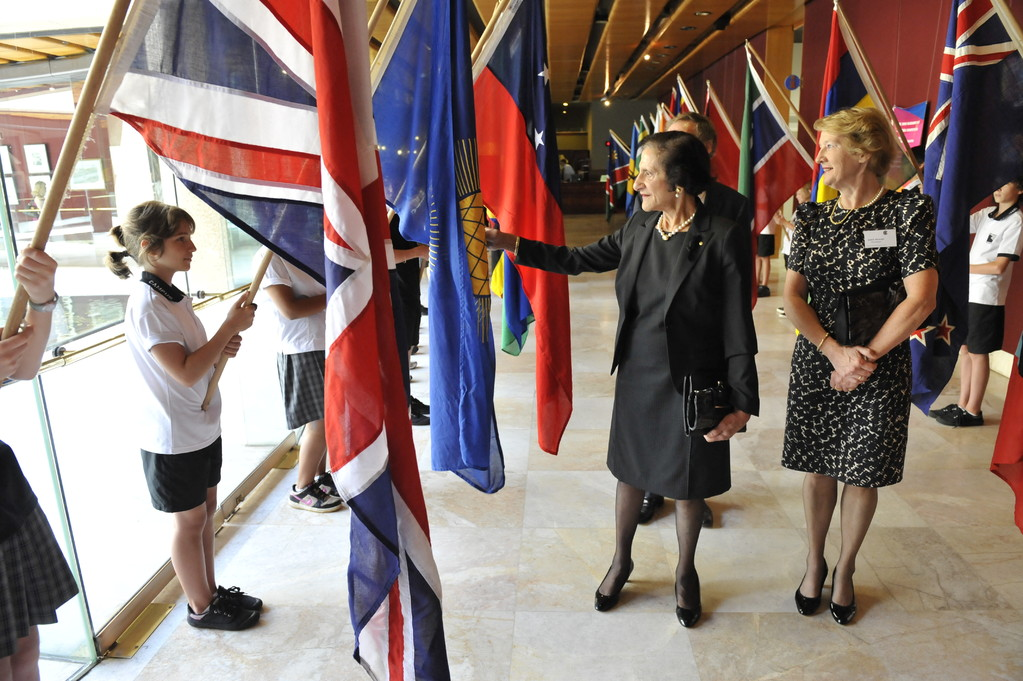 Her Excellency pointing out the Commonwealth of Nations flag