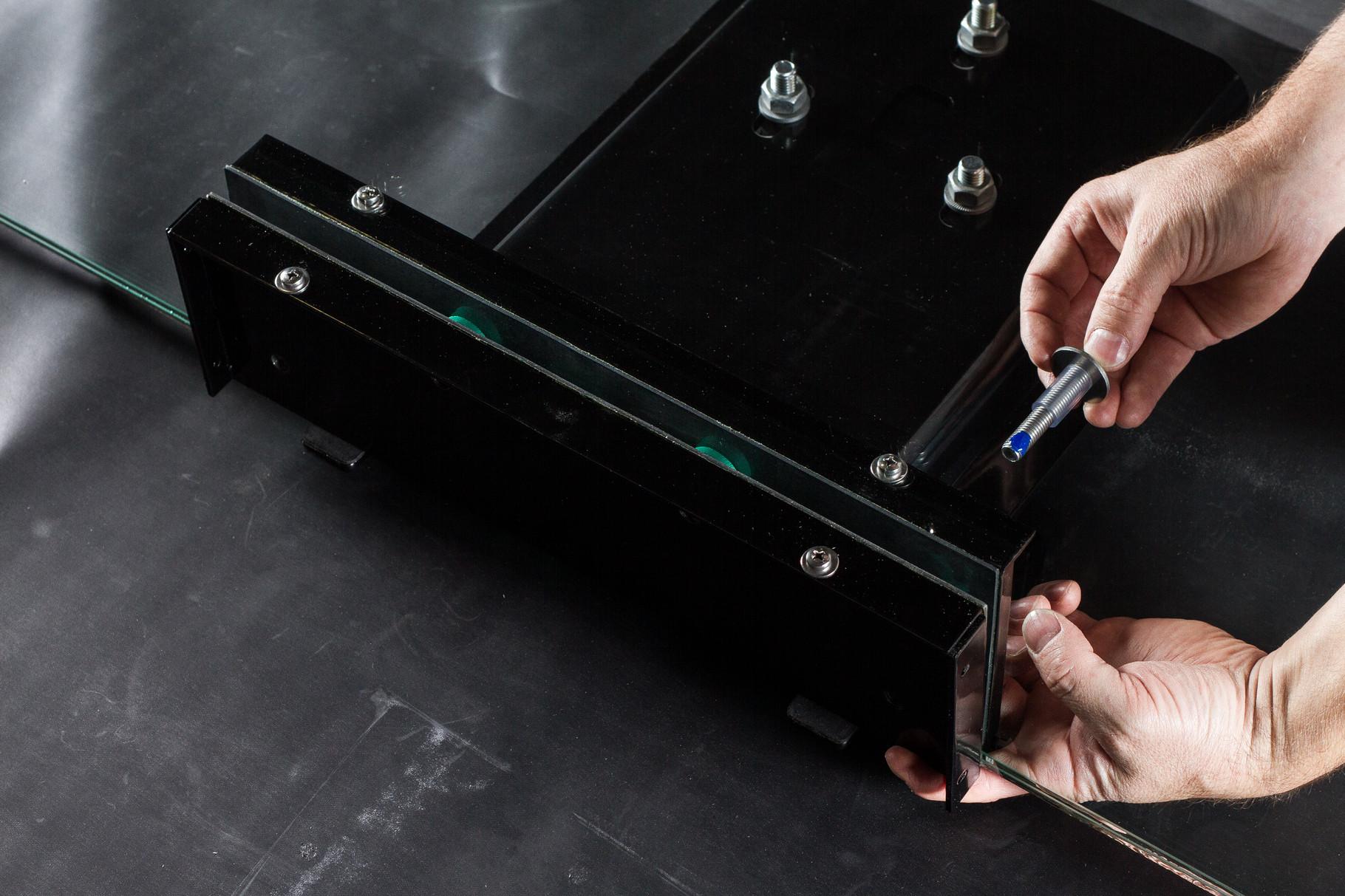 Den Schrauben gemeinsam mit dem Schutzschlauch inklusive Beilagscheibe durch die Glaskonsole führen und die Gegenplatte fixieren.