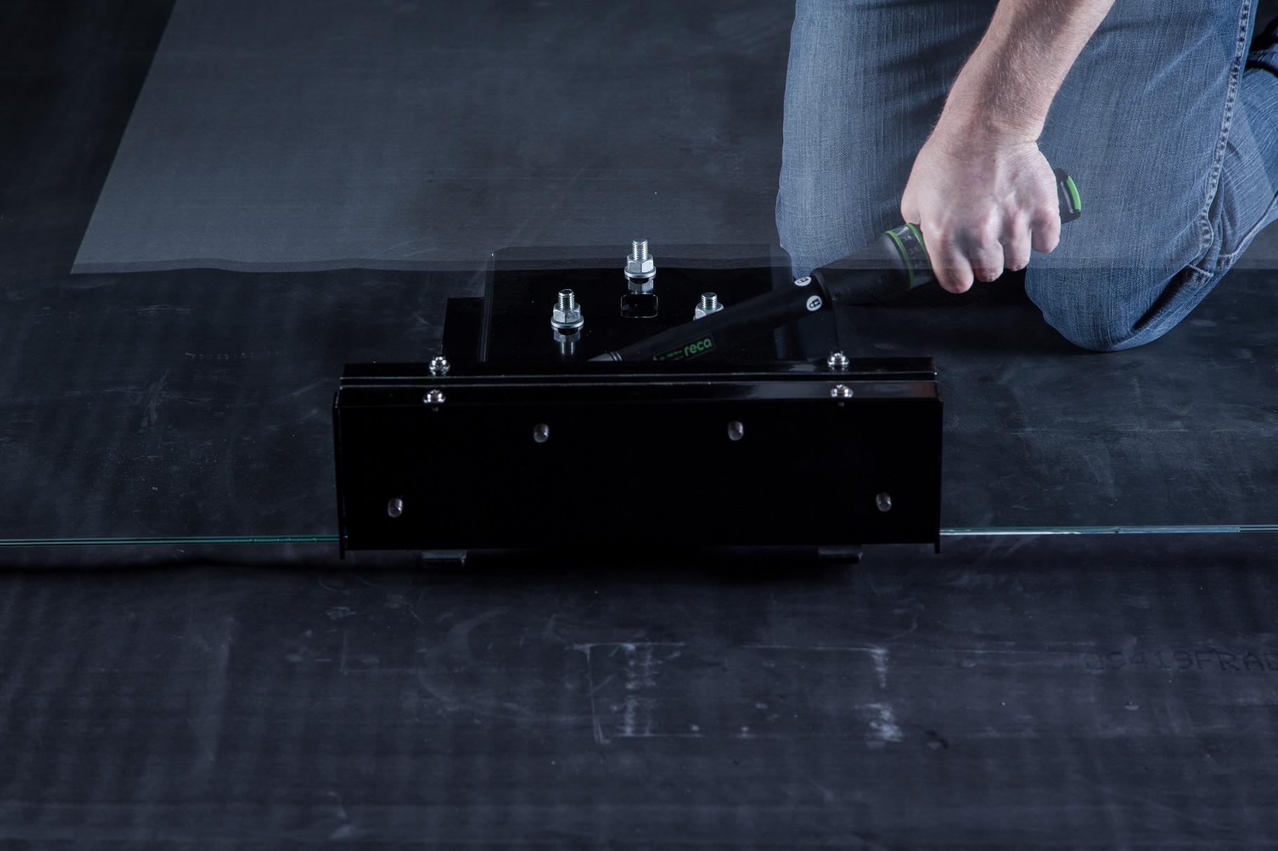 Die Schrauben der Glaskonsole/Gegenplatte mit dem Drehmomentschlüssel festziehen.