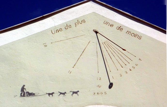 Hauteville-Lompnès : 102 rue Miguet, sur pignon. Cadran déclinant de l'après-midi, gravé et peint sur crépi lignes chiffrées en bout, en arc, style polaire, disque à œilleton en bout