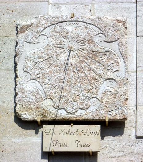Cormaranche-en-Bugey : église, sur la nef. Cadran légèrement déclinant du matin, gravé sur pierre lignes chiffrées en bout, encadrement baroque, style polaire sortant d'un soleil