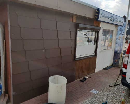 Vorher: Fassade mit alten dunklen Faserzementplatten