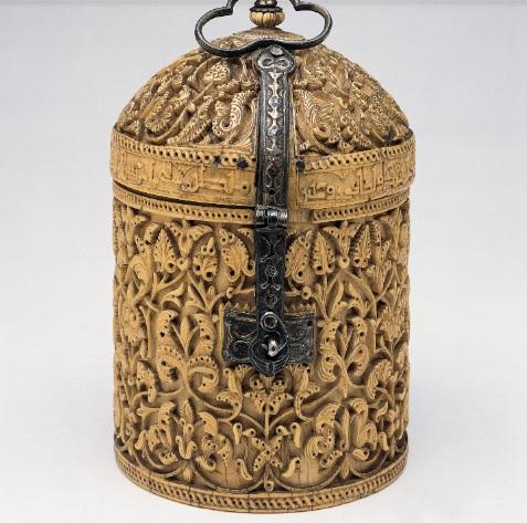 """Este píxide o jalaf del SX, esculpido en marfil representa la cumbre del arte islámico en la Península Ibérica. Su finalidad era contener perfumes de lujo con fines medicinales y eróticos.""""El aspecto que ofrezco es el mejor,seno de moza que no se abate"""""""