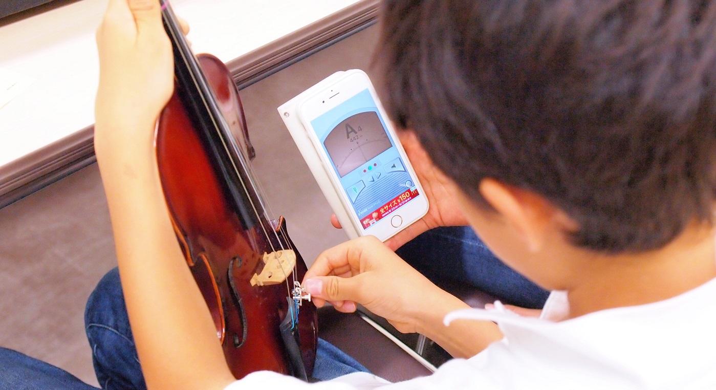 アプリを使って弦の音を正しく合わせています