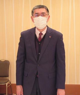 あいさつする岡本理事長