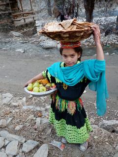 先祖の霊への供え物とみんなでシェアする食べ物を神殿に運ぶ少女