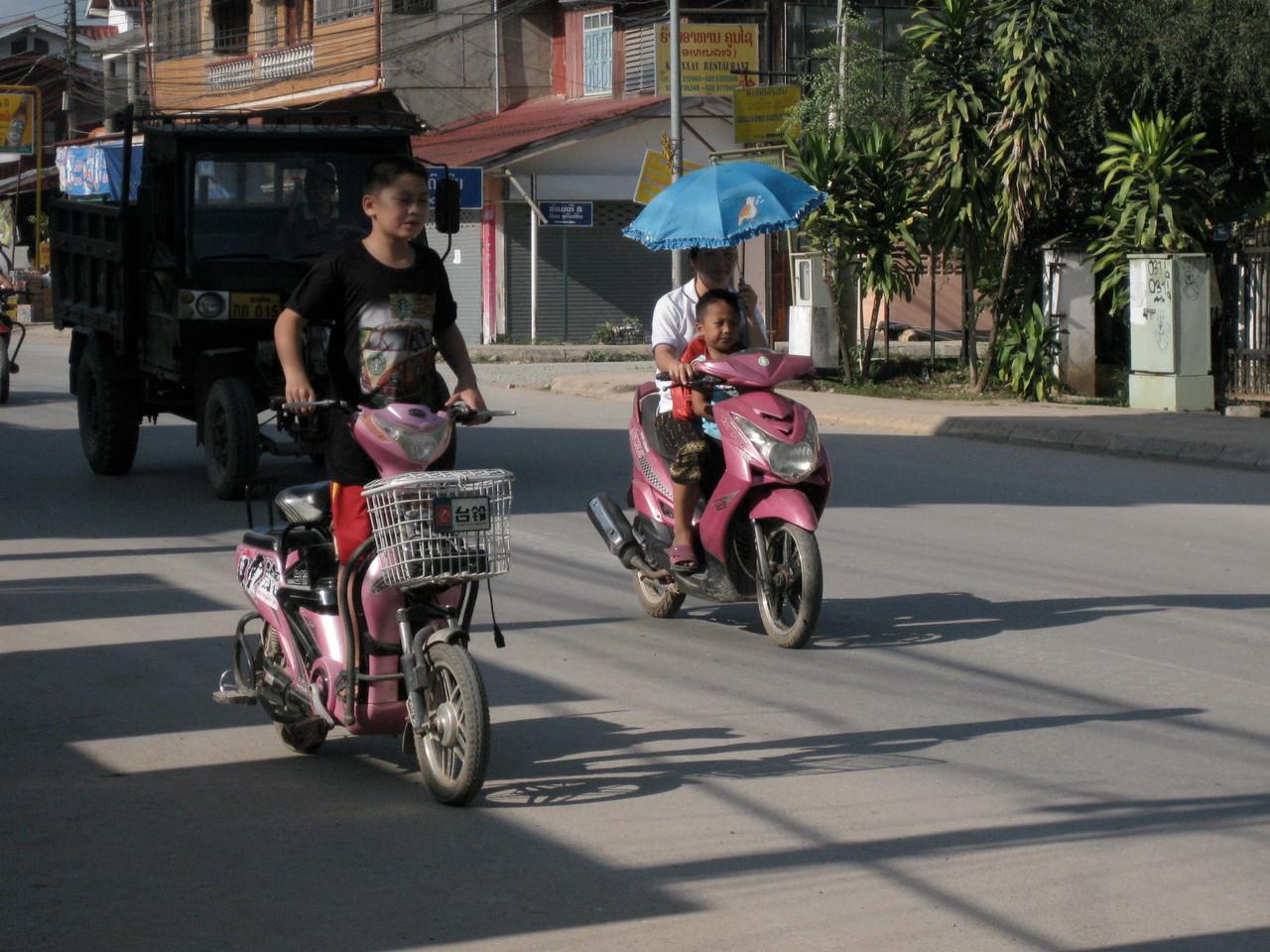 子供を乗せて片手運転。手前は子供のバイク運転。危ないじゃないか!