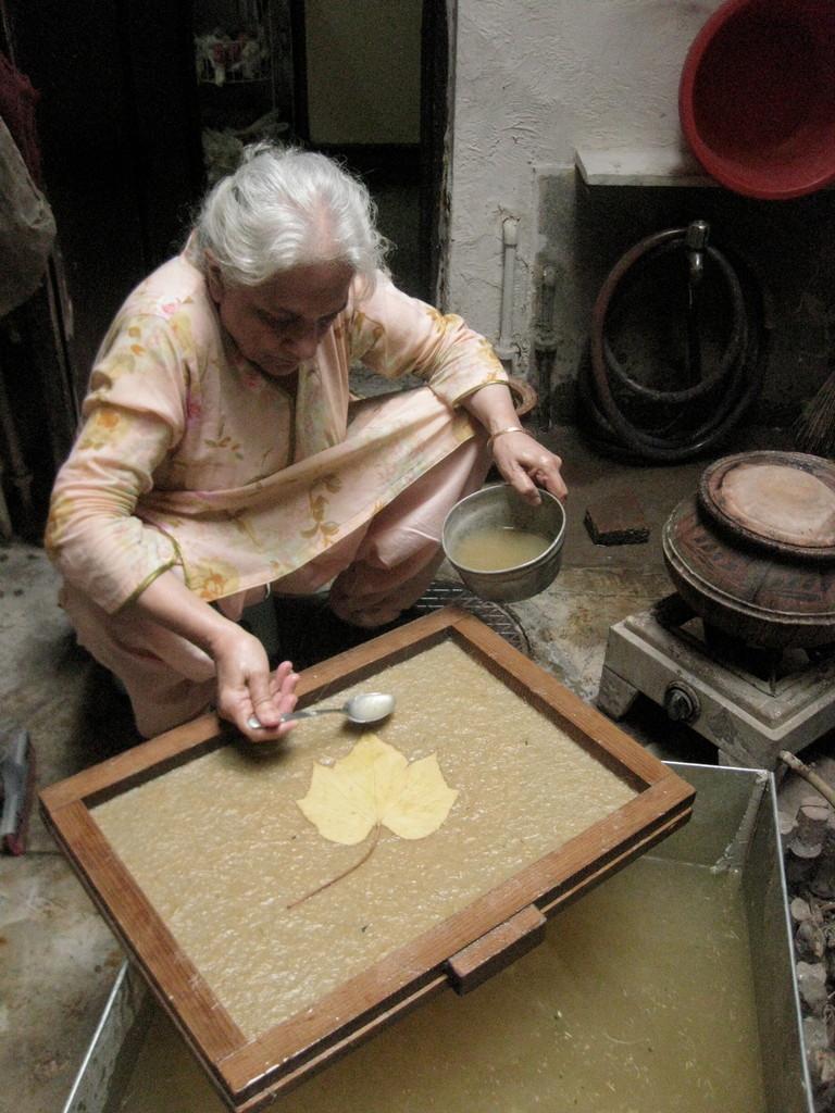 ドライリーフをあしらった手漉きの紙を作るヌザットさん。