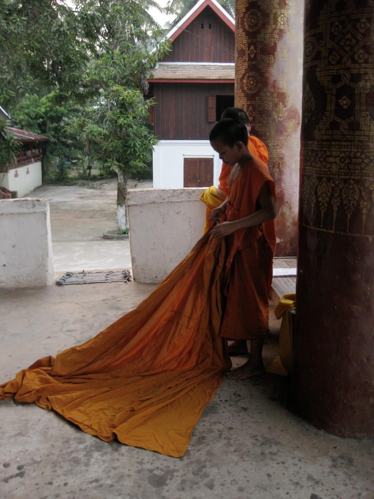 子供の修行僧は袈裟の着つけにちょっと苦労していた。