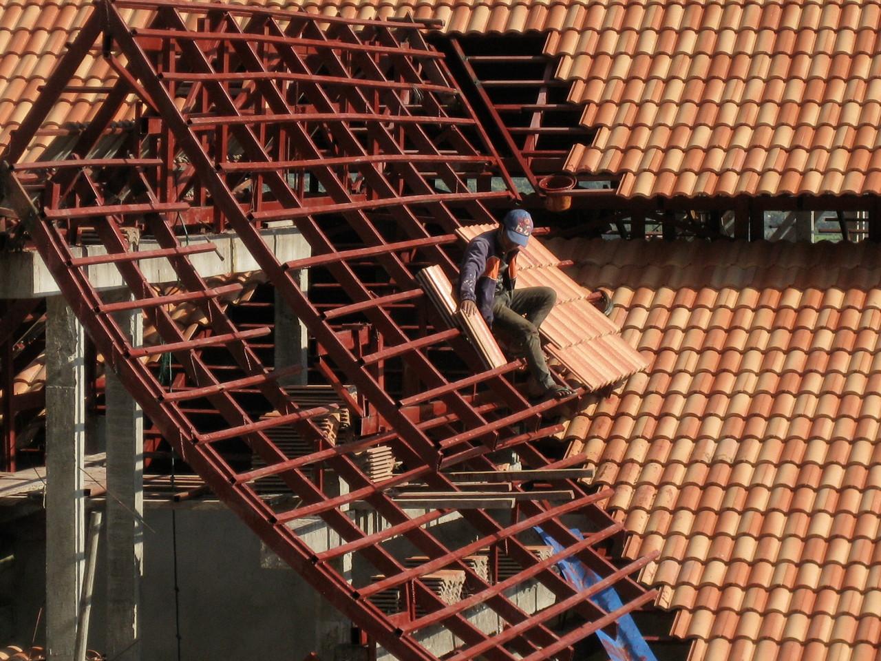 屋根を一枚一枚吹く職人。かなりの高さの上に陽射しも強い中目眩がしないだろうか