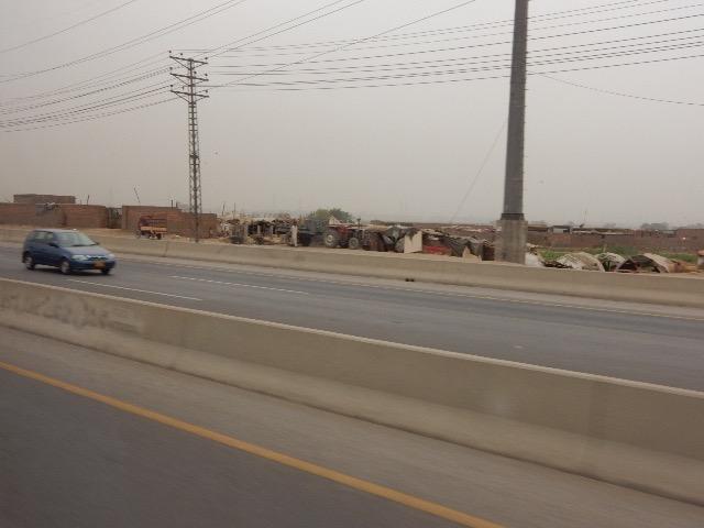 幅広い道路はガラガラ。向こうには粗末なテントの家々も見られる。