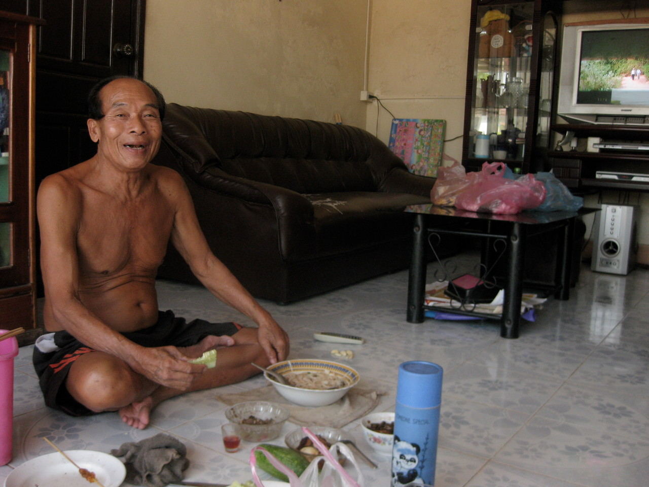 そのごはんを干したのを見ていたら、後から呼ばれて振り向くと、このおじさんの家があった。通りに面したシャッターは開かれて、すぐにおじさんの居間になっていた。朝からつまみを並べ、ラオラーオ(ラオスの焼酎)を飲みながら、べトナムのドラマを見ていた。どうも奥さんがハノイ出身のべトナム人らしい。(奥さんは買物に出かけたそうだ)私にも飲め飲めと赤いラオラーオを勧めてくれた。強かったけどけっこうおいしかった。
