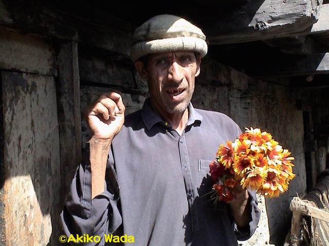 12年前の喪明けの行事で花を配る義兄。義兄は冠婚葬祭の行事には積極的に参加していた。