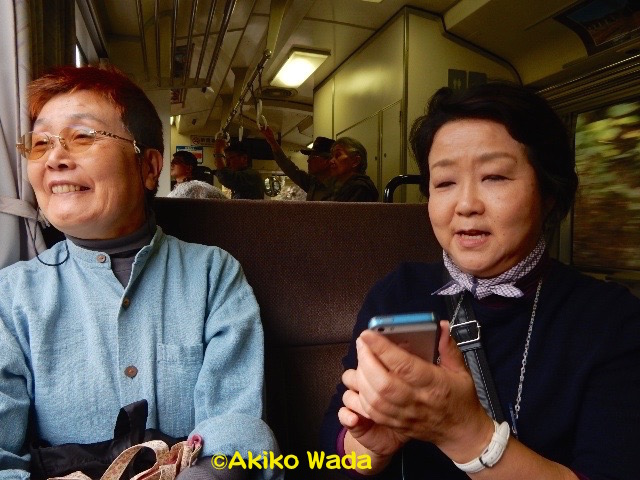 三江線の車窓からの景色を楽しむ友人たち。後ろにはマニヤックなおじさんたちが立って写真を撮っているのが見える。