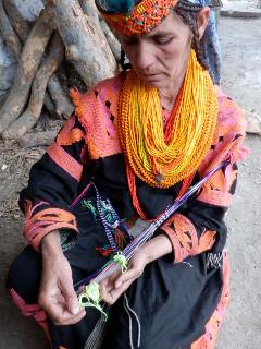 伝統的な織り紐を織るボンボレット谷の女性