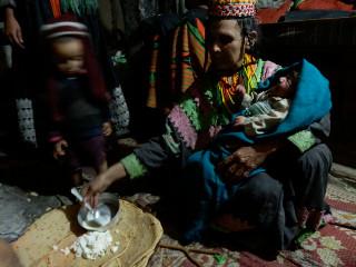 生後12日の赤ん坊のダックボーニャック(腰紐結い)儀礼。形式的に赤ん坊の口に食事を与える。