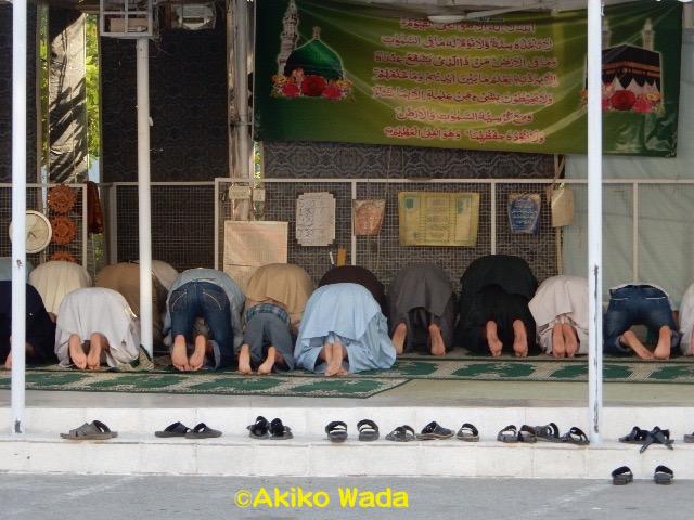 お祈りをする近くのマーケットの店員さんたち