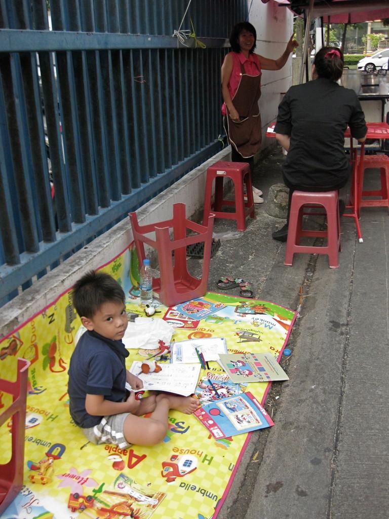 屋台で商売するお母さんのそばで、絵本で遊ぶ男の子。