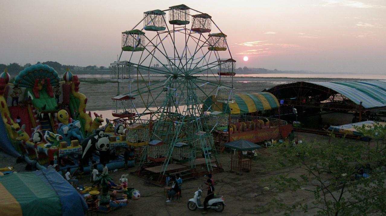 メコンに沈む夕日。川沿いのアヌヴォン王公園は夕方になると、遊園地やナイトマーケットが開き大勢の市民で賑わう。