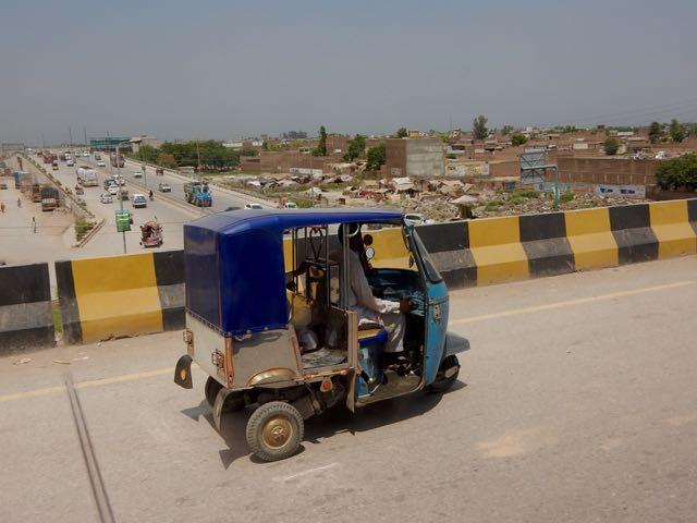 高速道路への立体道路を走るリキシャ。向こうにはアフガン難民のテント住宅も見える。