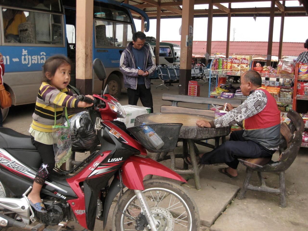 モーターバイクの女の子とカップラーメンを食べるおっさんと切符売りの兄さん。ルアンナムター長距離バス・ターミナルにて。
