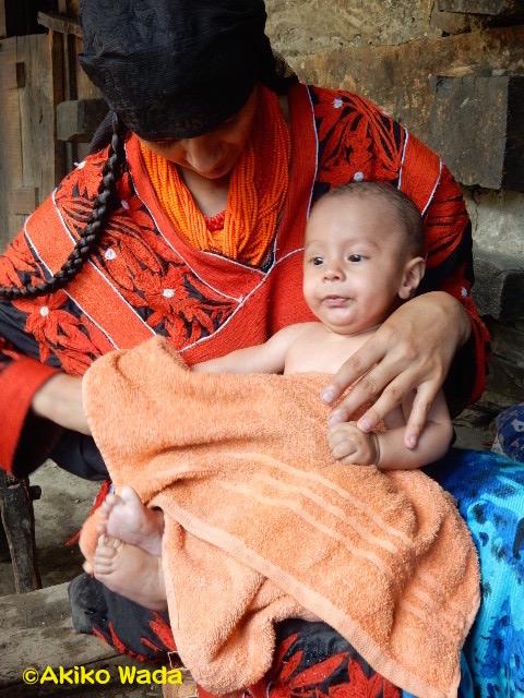グルパリックの行事の日、全身を洗ってもらった赤ん坊。といっても母親が片手で器から水をすくいなすりつけるたぐいのもので、使う水も1リットルほど。水はたくさんあるのにね。