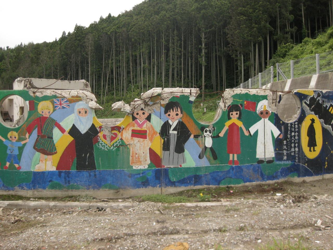 舞台壁に描かれた世界平和のメッセージを伝える児童たちの絵。