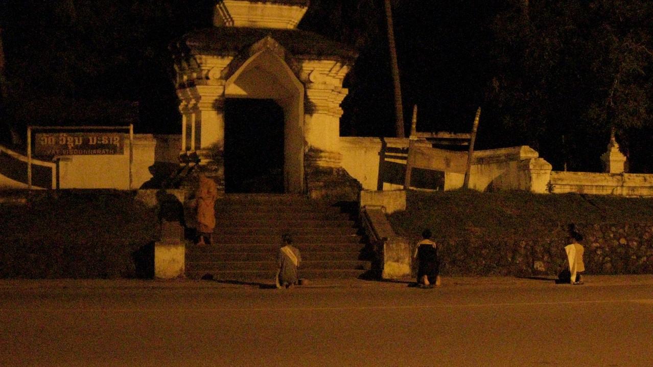 「僧侶の托鉢は朝何時に見れるか?」と宿の兄さんに聞いたら、「5時に僧侶たちがこの前を通る」と言うので、4時40分に起きて、5時前に自分で苦労して宿の錠を開けて外へ。外は真っ暗。たまにバイクが通るだけ。近くの寺院に行くが誰もいない。寺院の前を行ったり来たりしてると、ようやく揚げ物の屋台のおばさんが来たので、横に座って待つ。気がつくと、いつの間にかおひつを持った3人の女性がお寺の前に座っていた。5時半ぐらいだ。すると、お寺から年配の僧侶が1人出て来られた。