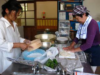 挽いた小麦をふるいにかけて再び挽き機にかける佳世さん。左はピザの準備をするNさん。