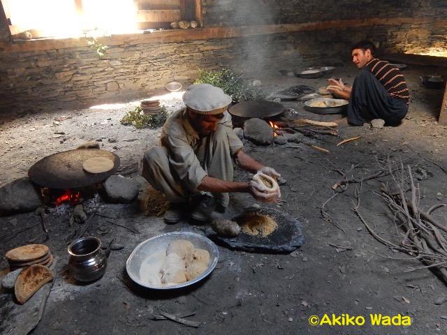 赤ん坊と母親が受ける浄めの儀礼のためのクルミパンを焼く家族の男性たち