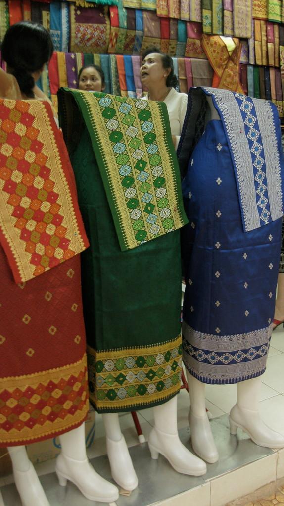 ラオスの女性の民族衣装の店もたくさんある。若い人はぴったりズボンやミニスカート姿が多いが、年配や会社勤めの女性はこの衣装を着けるようだ。