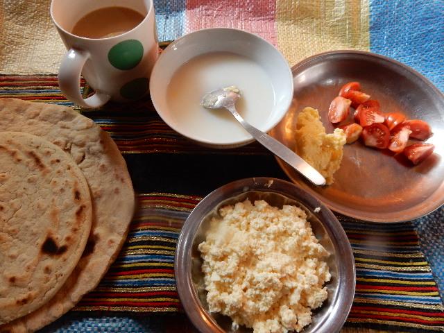 ある日の朝ごはん。左から小麦粉のパン(下)、トウモロコシ粉のパン(上)、ミルクティー、ニュウ(撹拌してバターを取った後のミルク汁)、カタックチャーシャ(子牛が生まれて初めて絞った乳で作る柔らかいチーズ)、バターとトマト。ミルクティーの他は全て親戚のところで獲れたもの。