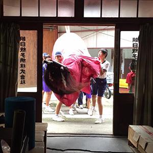朝日綟子網株式会社表玄関前に地元秋祭りの牛鬼を担ぐ子供たち
