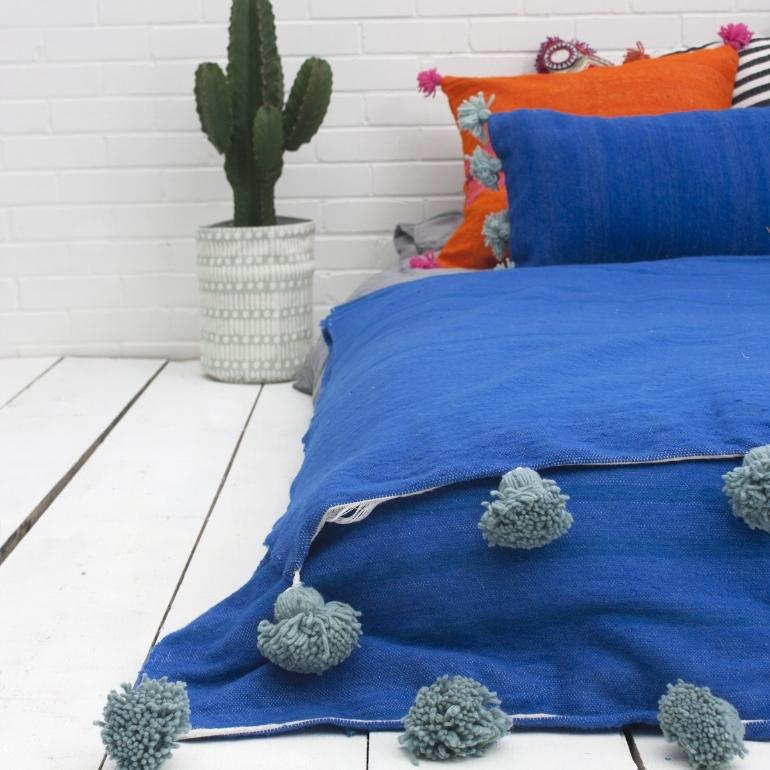 Überwurf fürs Bett in Blau mit Salbei PomPoms